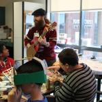 Adult man playing guitar to children making masks