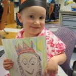 Small girl in homemade crown holding artwork