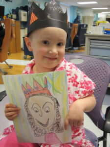 Small girl in homemade crown holding artwork