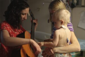 Woman playing guitar with baby and mother